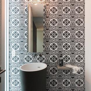 Immagine di un piccolo bagno di servizio contemporaneo con lavabo a colonna, pareti multicolore, top in cemento, piastrelle nere, piastrelle in ceramica, pavimento in cemento, WC monopezzo e pavimento nero