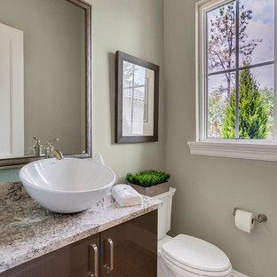 Aménagement d'un petit WC et toilettes classique avec un placard à porte plane, des portes de placard marrons, un WC à poser, un mur vert, un sol en carrelage de porcelaine, une vasque, un plan de toilette en granite et un sol multicolore.