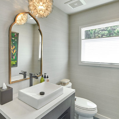 Powder room - large transitional ceramic tile and gray floor powder room idea in San Francisco with a two-piece toilet, gray walls, a vessel sink, solid surface countertops and white countertops