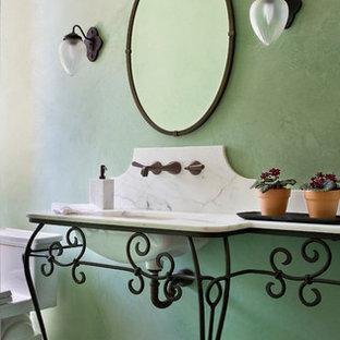 Неиссякаемый источник вдохновения для домашнего уюта: туалет в средиземноморском стиле с консольной раковиной, зелеными стенами и белой столешницей