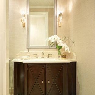 Стильный дизайн: туалет среднего размера в викторианском стиле с фасадами островного типа, темными деревянными фасадами, раздельным унитазом, бежевыми стенами, полом из керамической плитки, врезной раковиной, столешницей из искусственного камня и бежевым полом - последний тренд