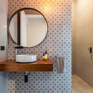 На фото: туалет среднего размера в современном стиле с разноцветной плиткой, настольной раковиной, серыми стенами, коричневой столешницей и столешницей из дерева