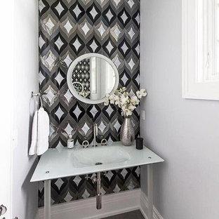 Foto de aseo actual, pequeño, con paredes multicolor, suelo de madera en tonos medios, lavabo suspendido y encimera de vidrio