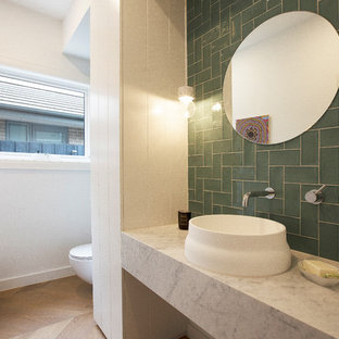 Photo of a modern powder room in Melbourne with green tile, white walls, medium hardwood floors, a vessel sink, beige floor and grey benchtops.