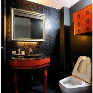 ニューヨークの小さいエクレクティックスタイルのおしゃれなトイレ・洗面所 (家具調キャビネット、赤いキャビネット、一体型トイレ、黒いタイル、磁器タイル、黒い壁、磁器タイルの床、一体型シンク、人工大理石カウンター、黒い床) の写真