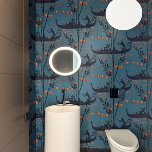 This is an example of a world-inspired cloakroom in Miami with multi-coloured walls, a pedestal sink and grey floors.