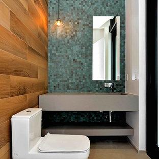 Foto di un piccolo bagno di servizio minimal con nessun'anta, ante grigie, WC monopezzo, piastrelle multicolore, piastrelle in ceramica, pareti blu, pavimento in pietra calcarea, lavabo integrato e top in quarzo composito
