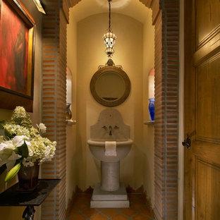 На фото: большой туалет в средиземноморском стиле с раковиной с пьедесталом, бежевыми стенами, полом из терракотовой плитки, оранжевой плиткой и терракотовой плиткой с