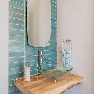 Пример оригинального дизайна: туалет в современном стиле с настольной раковиной, столешницей из дерева, синей плиткой, разноцветными стенами и коричневой столешницей