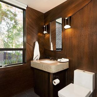 Inredning av ett modernt mellanstort toalett, med skåp i mörkt trä, en toalettstol med hel cisternkåpa, bruna väggar, klinkergolv i porslin, ett undermonterad handfat, bänkskiva i travertin, grått golv och släta luckor