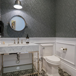 Example of a small transitional multicolored floor powder room design in Phoenix with a two-piece toilet, gray walls, a console sink, gray countertops, furniture-like cabinets and marble countertops