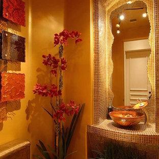 Exemple d'un WC et toilettes méditerranéen de taille moyenne avec un placard sans porte, un WC à poser, un carrelage marron, un carrelage jaune, carrelage en mosaïque, un mur jaune, un sol en carrelage de céramique, une vasque, un plan de toilette en verre et un sol gris.