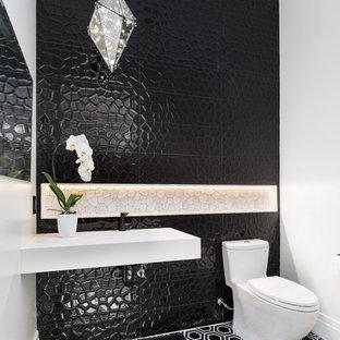 Идея дизайна: туалет в современном стиле с черной плиткой, белыми стенами, подвесной раковиной, разноцветным полом и серой столешницей