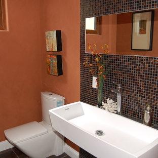 Cette image montre un petit WC et toilettes design avec un carrelage rouge, un mur rouge et une grande vasque.