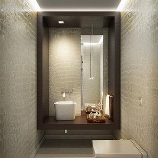 Пример оригинального дизайна: туалет среднего размера в современном стиле с коричневыми фасадами, инсталляцией, бежевой плиткой, керамической плиткой, бежевыми стенами, бетонным полом, настольной раковиной, столешницей из дерева и бежевым полом