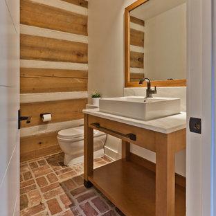Immagine di un bagno di servizio nordico di medie dimensioni con consolle stile comò, ante in legno scuro, WC monopezzo, pareti bianche, pavimento in mattoni, lavabo a bacinella e top in marmo