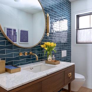 Country Gästetoilette mit verzierten Schränken, dunklen Holzschränken, Wandtoilette, blauen Fliesen, weißer Wandfarbe, hellem Holzboden, Unterbauwaschbecken und weißer Waschtischplatte in New York