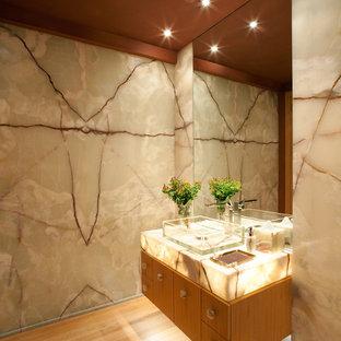 Стильный дизайн: туалет среднего размера в современном стиле с плоскими фасадами, фасадами цвета дерева среднего тона, бежевой плиткой, плиткой из листового камня, разноцветными стенами, полом из бамбука, настольной раковиной, столешницей из оникса и бежевым полом - последний тренд