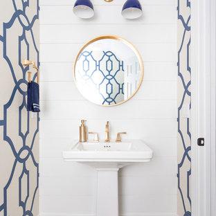 Exemple d'un WC et toilettes bord de mer de taille moyenne avec un mur bleu, un sol en bois clair, un lavabo de ferme et un sol gris.