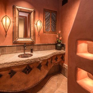 Inspiration pour un WC et toilettes sud-ouest américain de taille moyenne avec des carreaux de porcelaine, un mur orange, un sol en carreau de terre cuite et un plan de toilette en granite.