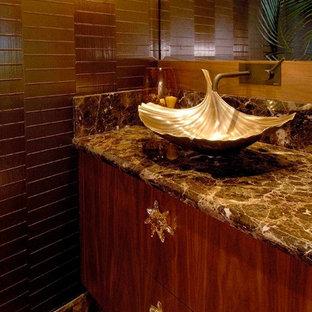 Cette photo montre un WC et toilettes exotique avec un placard à porte plane, des portes de placard en bois brun, un WC à poser, un carrelage marron, un carrelage de pierre, un mur marron, un sol en marbre, une vasque et un plan de toilette en marbre.