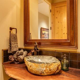 Imagen de aseo rústico, pequeño, con lavabo sobreencimera, encimera de madera, paredes amarillas y encimeras marrones