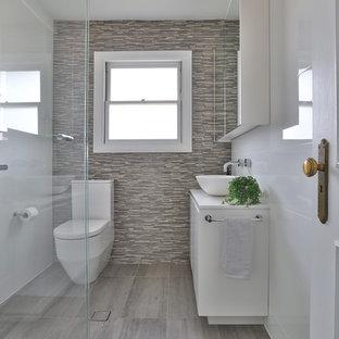 На фото: туалет среднего размера в современном стиле с белыми фасадами, полом из керамической плитки, столешницей из искусственного кварца, серым полом, белой столешницей, раздельным унитазом, бежевой плиткой, плоскими фасадами, удлиненной плиткой и настольной раковиной с