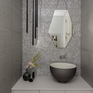 Свежая идея для дизайна: маленький туалет в современном стиле с плоскими фасадами, серыми фасадами, серой плиткой, стеклянной плиткой, серыми стенами и настольной раковиной - отличное фото интерьера