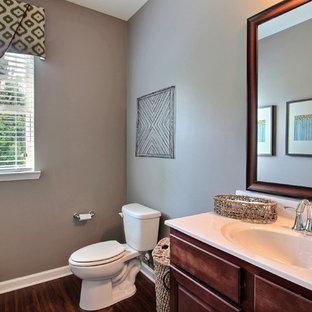 Идея дизайна: большой туалет в классическом стиле с унитазом-моноблоком, полом из ламината, монолитной раковиной, мраморной столешницей, фасадами в стиле шейкер, темными деревянными фасадами, серой плиткой, серыми стенами и коричневым полом