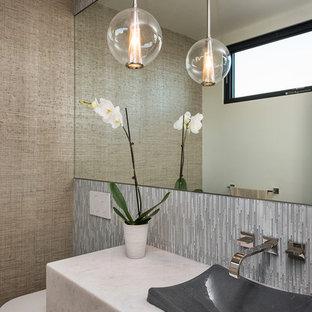 Bild på ett funkis vit vitt toalett, med en vägghängd toalettstol, grå kakel, bruna väggar, ett fristående handfat, marmorbänkskiva, brunt golv, stickkakel och mörkt trägolv