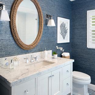 マイアミの中くらいのビーチスタイルのおしゃれなトイレ・洗面所 (白いキャビネット、青いタイル、青い壁、アンダーカウンター洗面器、フラットパネル扉のキャビネット、モザイクタイル、大理石の洗面台、マルチカラーの床、白い洗面カウンター) の写真