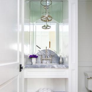 Idées déco pour un WC et toilettes bord de mer avec un placard avec porte à panneau encastré, des portes de placard blanches, un mur blanc, un lavabo encastré, un sol gris, un plan de toilette gris, meuble-lavabo encastré et du lambris.