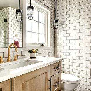 На фото: туалет среднего размера в стиле современная классика с фасадами в стиле шейкер, фасадами цвета дерева среднего тона, белой плиткой, плиткой кабанчик, белыми стенами, раздельным унитазом, врезной раковиной, столешницей из кварцита и белой столешницей