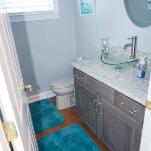 Foto di un piccolo bagno di servizio tradizionale con ante in stile shaker, ante grigie, WC a due pezzi, pareti grigie, pavimento in legno massello medio, lavabo a bacinella e top in granito