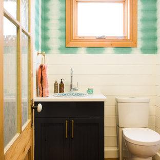 Exemple d'un petit WC et toilettes tendance avec un placard à porte shaker, des portes de placard noires, un WC à poser, un mur blanc, béton au sol, un lavabo posé, un plan de toilette en verre recyclé et un sol marron.