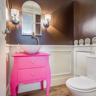Cette photo montre un petit WC et toilettes avec un lavabo posé, un placard en trompe-l'oeil, un plan de toilette en bois, un WC à poser, un mur multicolore, un sol en vinyl et un plan de toilette rose.
