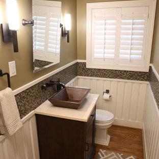 Inspiration pour un WC et toilettes craftsman de taille moyenne avec un placard en trompe-l'oeil, des portes de placard en bois sombre, un WC séparé, carrelage en mosaïque, un sol en bois clair, une vasque, un plan de toilette en quartz modifié et un carrelage marron.