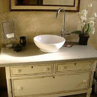 Cette image montre un WC et toilettes style shabby chic de taille moyenne avec des portes de placard blanches, un placard en trompe-l'oeil, un mur beige, un sol en carrelage de céramique, une vasque, un plan de toilette en stratifié et un sol beige.