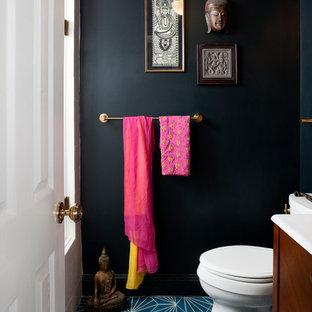 На фото: туалет среднего размера в стиле фьюжн с консольной раковиной, темными деревянными фасадами, унитазом-моноблоком, синей плиткой, черными стенами и бетонным полом с