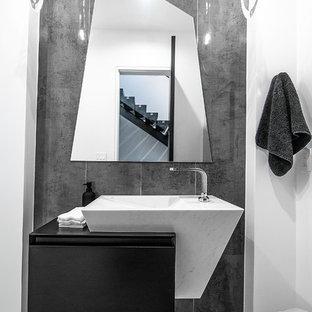 Свежая идея для дизайна: туалет в современном стиле с плоскими фасадами, черными фасадами, серой плиткой, серыми стенами, серым полом и черной столешницей - отличное фото интерьера