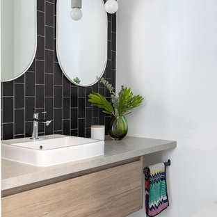 Inspiration for a mid-sized contemporary powder room in Brisbane with medium wood cabinets, a one-piece toilet, black and white tile, ceramic tile, white walls, cement tiles, engineered quartz benchtops, grey floor, grey benchtops, flat-panel cabinets and a drop-in sink.