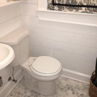 ニューヨークの小さいトランジショナルスタイルのおしゃれなトイレ・洗面所 (ガラス扉のキャビネット、白いキャビネット、一体型トイレ、白いタイル、大理石タイル、グレーの壁、大理石の床、壁付け型シンク、大理石の洗面台、グレーの床) の写真