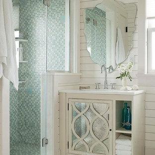 Idée de décoration pour un petit WC et toilettes design avec des portes de placard blanches, un carrelage bleu, un carrelage en pâte de verre, un mur blanc, un lavabo encastré, un plan de toilette en quartz modifié et un plan de toilette blanc.