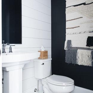 Cette image montre un WC et toilettes rustique avec un WC séparé, un mur noir, un sol en bois foncé, un lavabo de ferme et un sol marron.