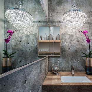 Inspiration for an industrial powder room remodel in Santa Barbara with gray walls, an undermount sink, wood countertops and brown countertops