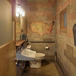 Réalisation d'un WC et toilettes urbain avec un mur gris, béton au sol, un placard sans porte, des portes de placard en bois sombre, un WC séparé, du carrelage en ardoise, un lavabo suspendu, un plan de toilette en bois et un sol gris.