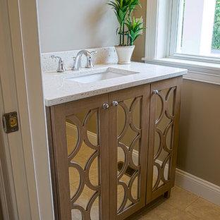 Aménagement d'un WC et toilettes classique de taille moyenne avec un placard à porte shaker, des portes de placard en bois brun, un mur beige, un sol en calcaire, un lavabo encastré, un plan de toilette en terrazzo et un sol beige.