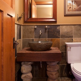 Medium sized traditional cloakroom in Minneapolis with a vessel sink, wooden worktops, a one-piece toilet, slate flooring, freestanding cabinets, medium wood cabinets, beige walls, slate tiles, grey tiles and brown worktops.