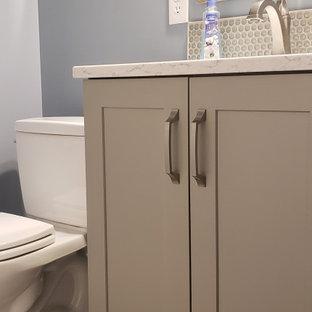 Cette photo montre un petit WC et toilettes chic avec un placard à porte shaker, des portes de placard grises, un WC séparé, un carrelage gris, des plaques de verre, un mur bleu, un lavabo encastré, un plan de toilette en quartz modifié, un plan de toilette blanc et meuble-lavabo encastré.