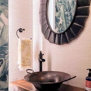 Aménagement d'un petit WC et toilettes exotique avec un placard à porte persienne, des portes de placard noires, un mur beige, une vasque, un plan de toilette en bois, un plan de toilette marron et meuble-lavabo sur pied.